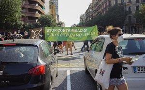 Miembros de Eixample Respira despliegan una pancarta contra la contaminación en la calle de Aragó, esta tarde