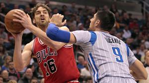 Pau Gasol trata de pasar el balón ante la defensa de Nikola Vucevic, en el partido entre los Bulls y los Magic.