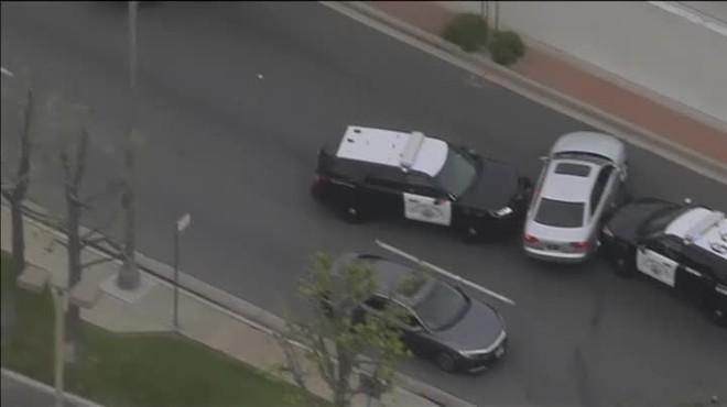 Parecía que dos coches de policía habían acorralado al ladrón de un vehículo cuando consigue escapar conduciendo de un lado a otro de la carretera.