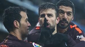 Piqué, entre Busquets y Suárez, pide silencio en Cornellà tras anotar el 1-1.