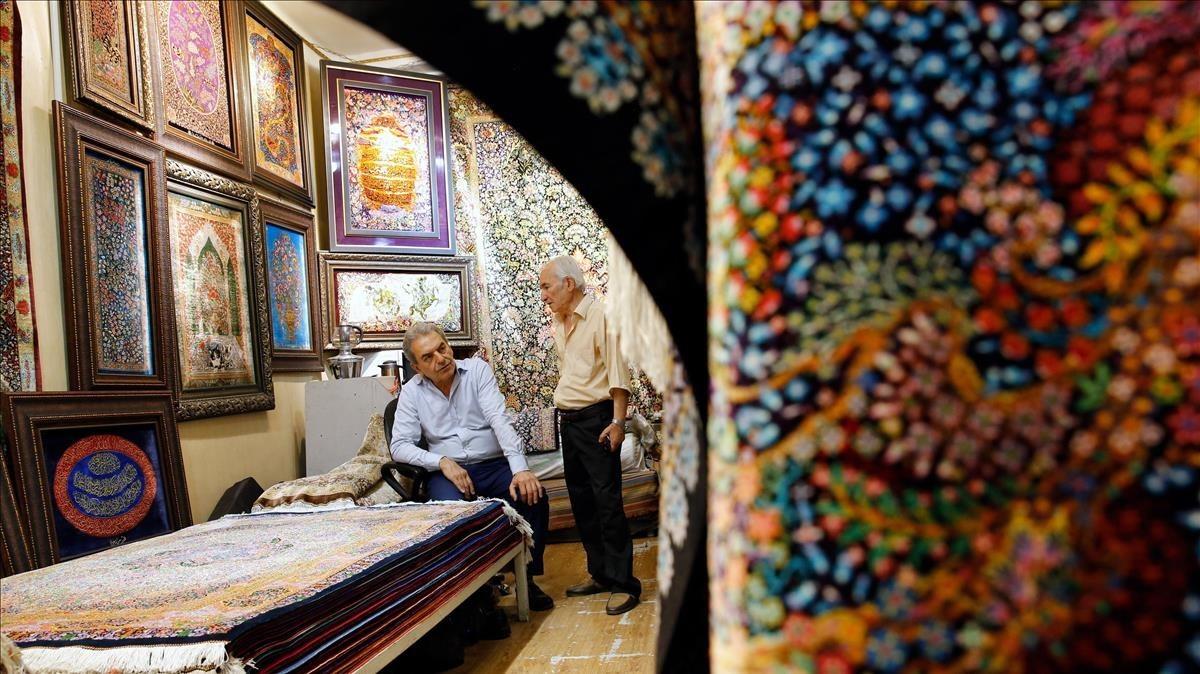 Dos hombres iranís conversan dentro de su negocio de alfombras en el Gran Bazar de Teherán.
