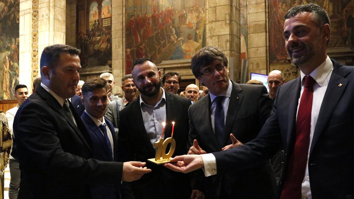 >El president, Carles Puigdemont, y el conseller de Empresa i Coneixement, Santi Vila, este martes, 1 de agosto, en la recepción en la Generalitat a los organizadores del Circuit Festival, con una tarta de aniversario.