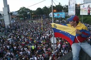 Un simpatizante de la oposición ondea una bandera venezolana ante cientos de personas congregadas para celebrar los resultados electorales en Venezuela.
