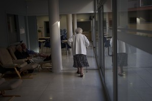 Una mujer pasea en soledad por los pasillos de una residencia.