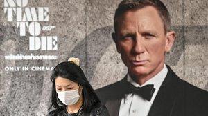 Una mujer con mascarilla frente al cartel de 'No time to die'.