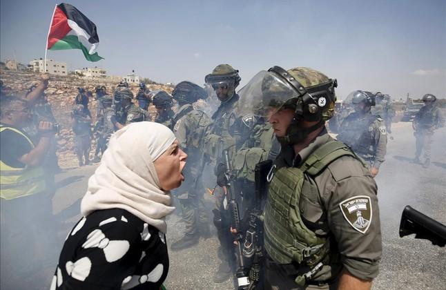Una mujer palestina discute con un policía fronterizo israelí durante una protesta contra los asentamientos judíos en la aldea cisjordana de Nabi Saleh, cerca de Ramala.