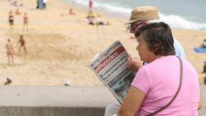Una pareja lee EL PERIÓDICO en Barcelona.