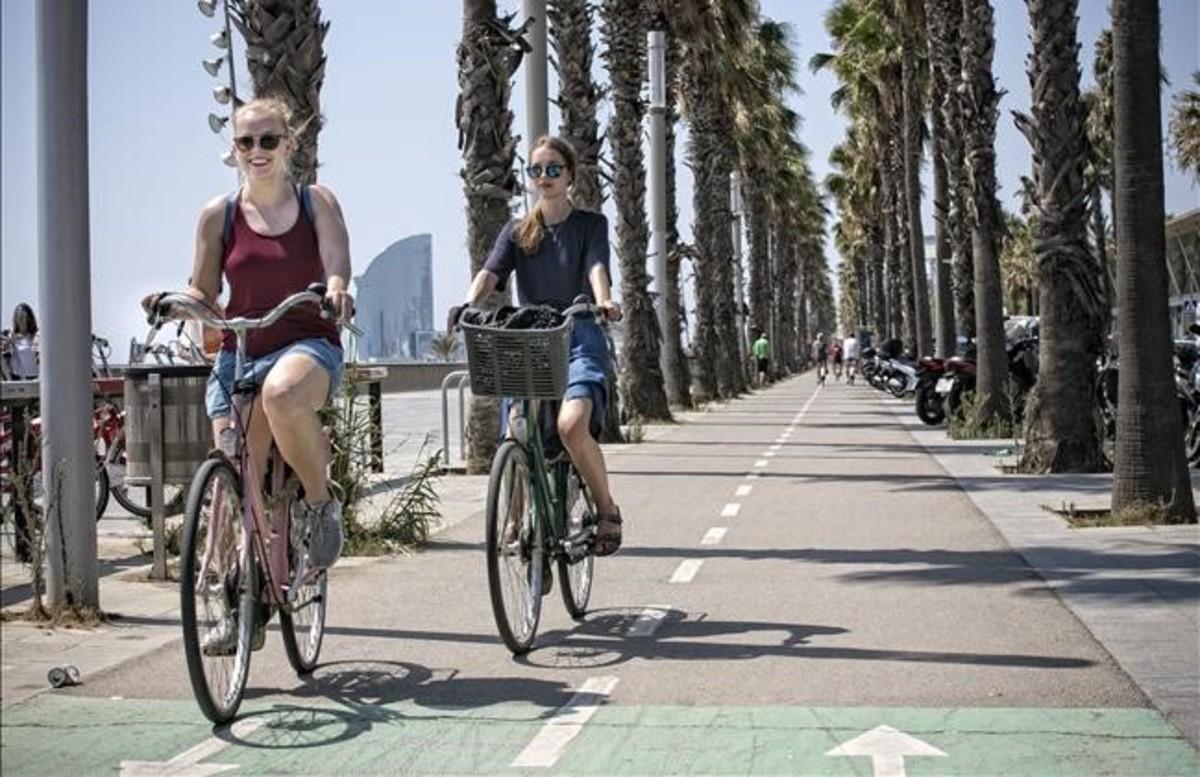 Unos ciclistas circulan por el carril bici ubicado frente al Hospital del Mar, en la Vila Olímpica de Barcelona.