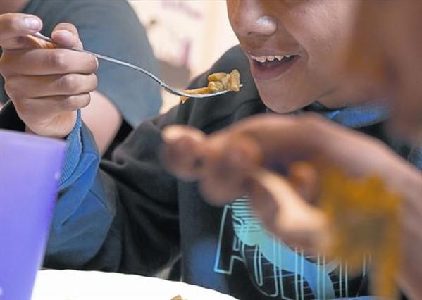 Unos niños en un comedor social de una entidad en el barrio del Raval, en Barcelona.
