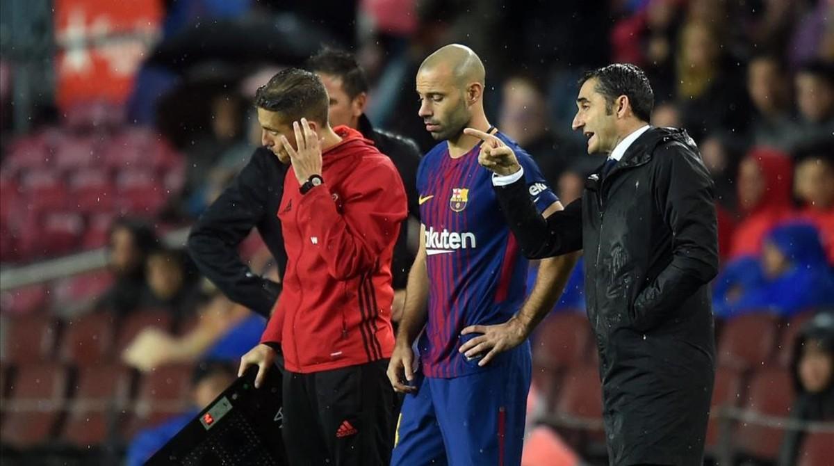 Valverde da instrucciones a Mascherano antes de que entre en juego.