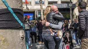Varias personas lloran tras depositar flores en el lugar en el que fue asesinado un policia durante un ataque yihadista perpetrado en la avenida de los Campos Eliseos de París.