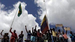 Un grupo de gente protesta en la frontera entre Brasil y Venezuela.