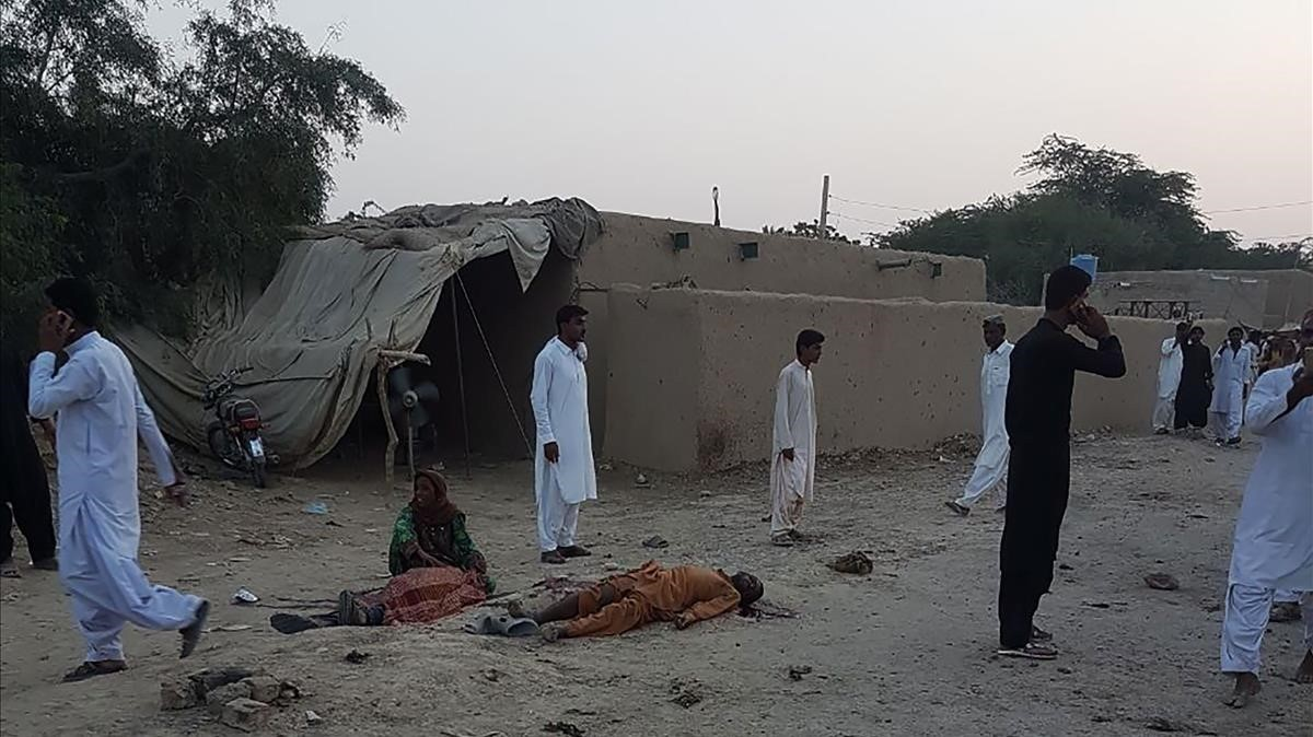 Algunos fieles deambulan junto a los cuerpos de las víctimas del atentado en Pakistán, este jueves.