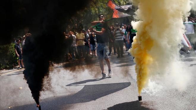 Manifestantes entre bengalas de humo