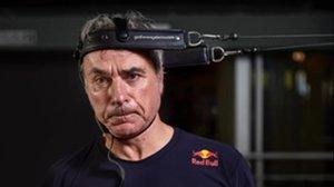 Carlos Sainz con el rostro desencajado, haciendo ejercicios para fortalecer su cuello.