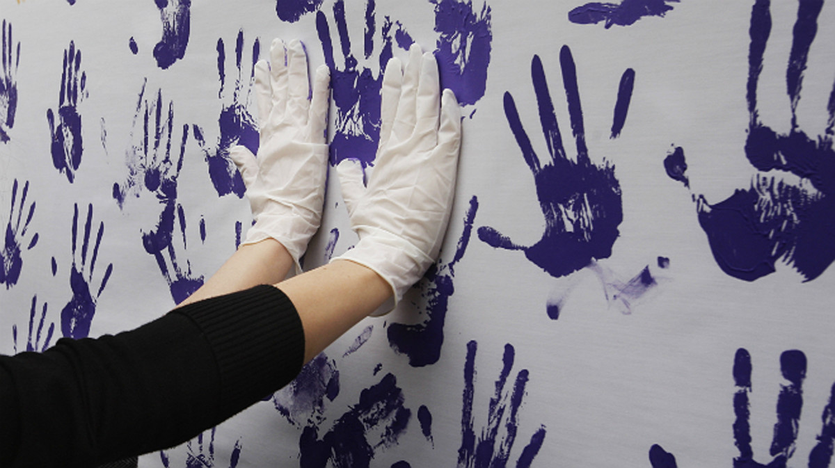 Una pared con manos lilas pintadas en un acto feminista