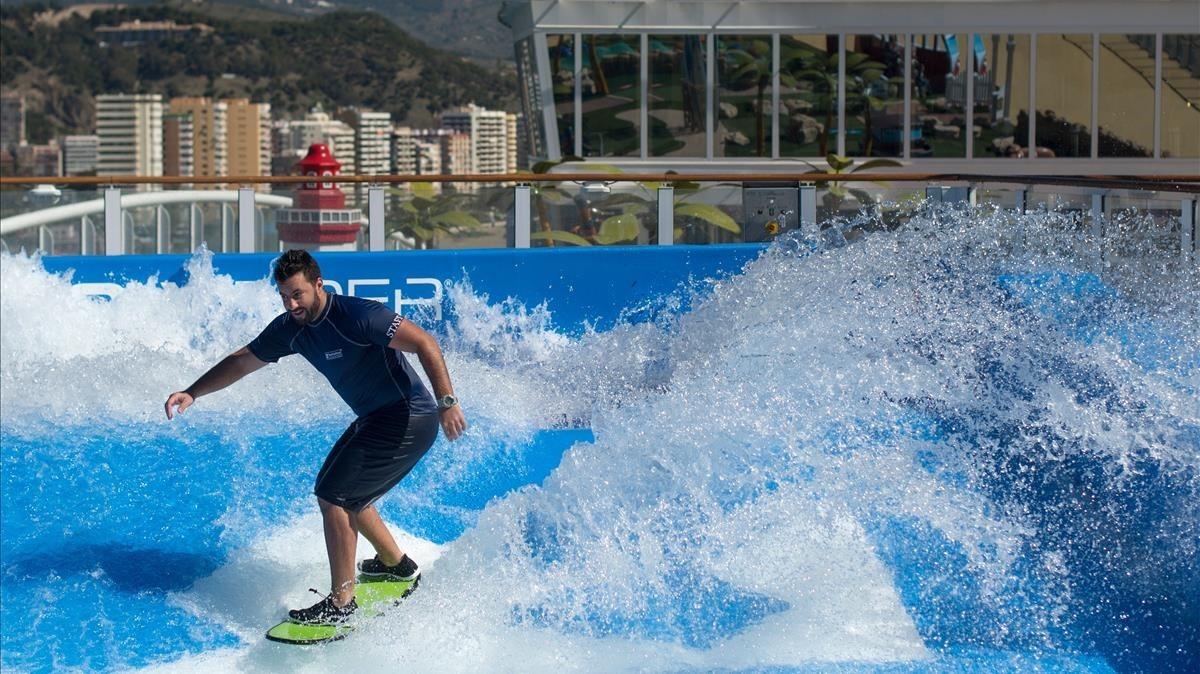 Un deportista hace surf en una de las piscinas del buque.