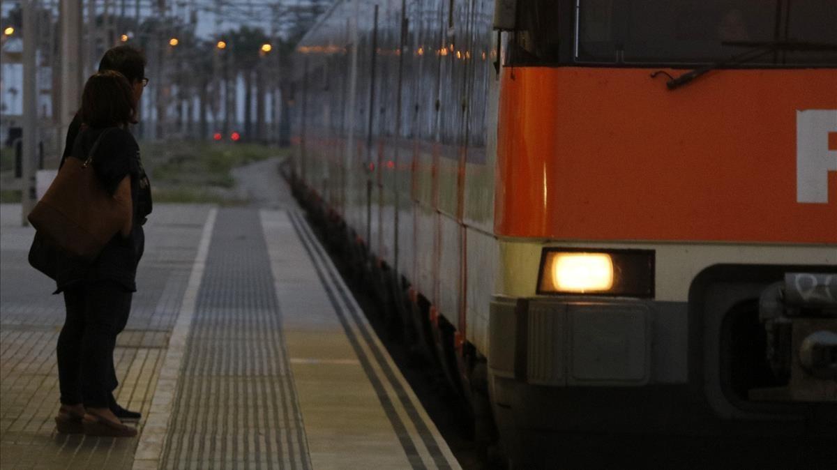Dos pasajeros en la andana de la estación de Mataró.
