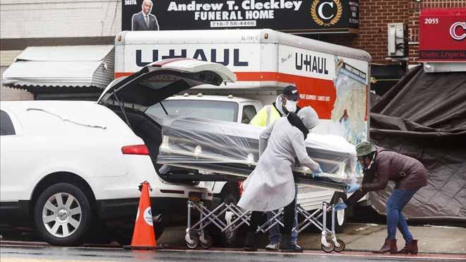 Estados Unidos supera los 100.000 muertos por coronavirus. En la foto, trabajadores de una funeraria de Brooklyn introducen un ataúd de una víctima de covid-19 en un coche fúnebre.