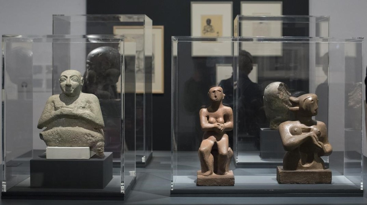 Figura de piedra sentada en actitud de oración del 2500 a.C. (izquierda) junto a dos esculturas de Henry Moore de 1929expuestas en la Fundació Miró.