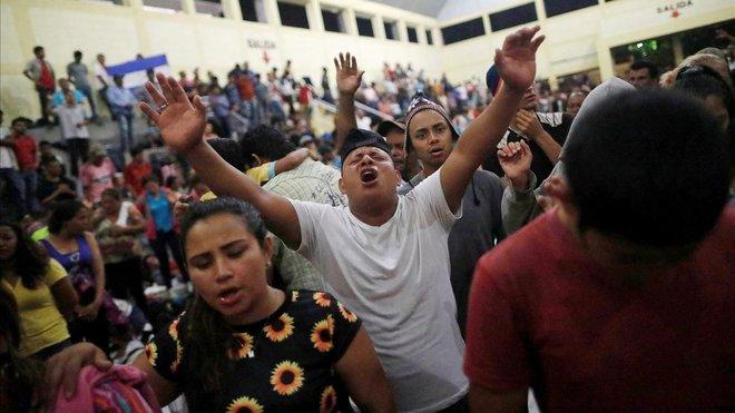 Hondureños rezan en un refugio provisional en Chiquimula, Guatemala
