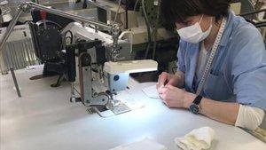 Una empleadade la empresaArmani trabaja en la elaboración de batas sanitarias en Verona.