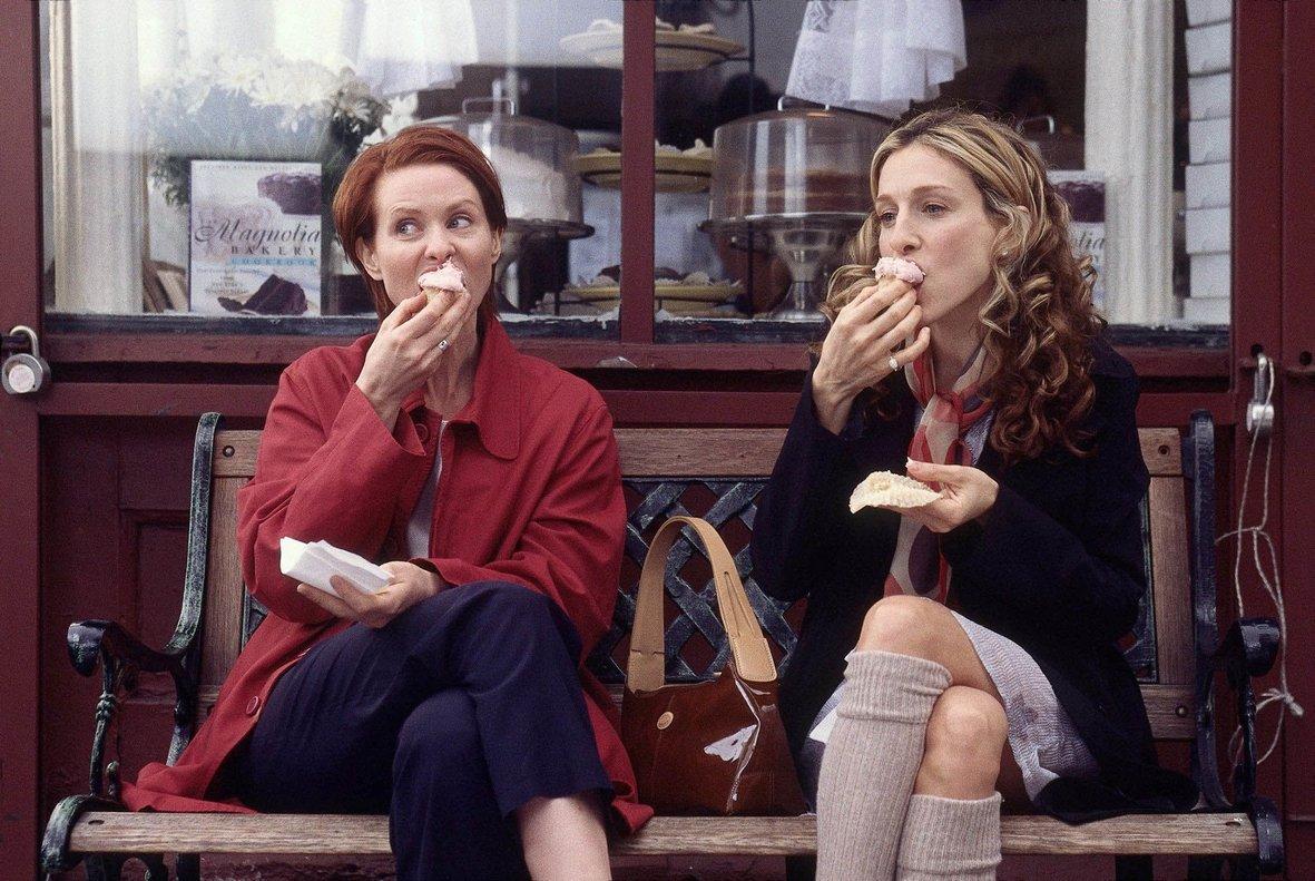 Miranda Hobbes (Cynthia Nixon) y Carrie Bradshaw (Sarah Jessica Parker)comen'cupcakes' y hablandel amor frente a la pastelería Magnolia Bakery, en una escena de 'Sexo en Nueva York'.