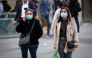 Mujeres caminan con mascarillas por el coronavirus.