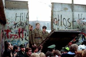 Guardias fronterizos de Alemania Oriental observan cómo la multitud de trae al piso un lado del muro.