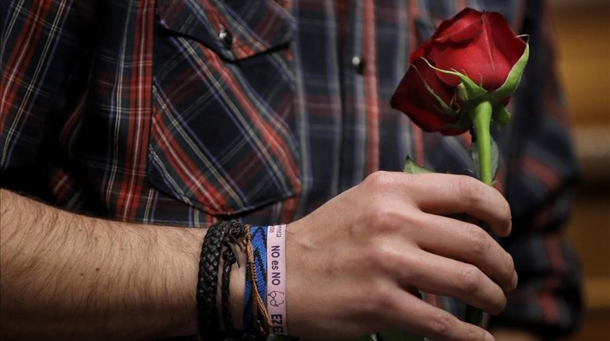 Iglesias sostiene una rosa con la mano en la que luce una pulsera podemista con el lema de Sánchez contra la abstención del PSOE en la investidura de Rajoy.