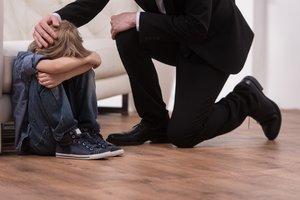 Un padre consuela a su hijo que está llorando.
