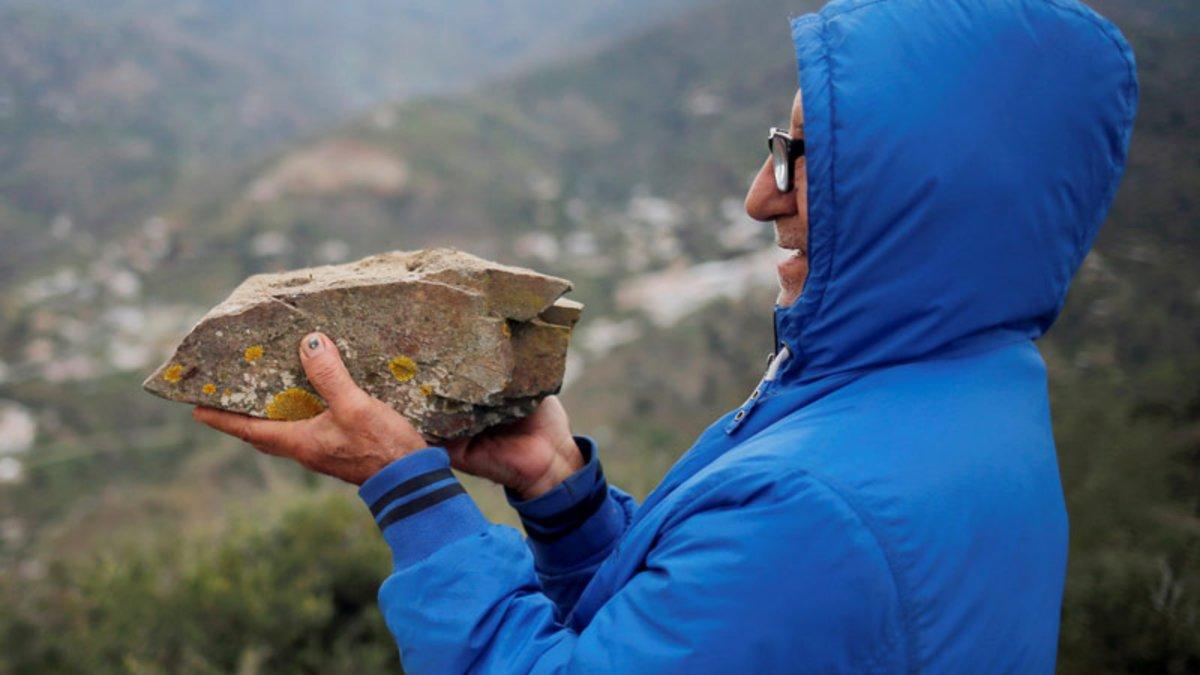 Un lugareño sostiene una piedra de pizarra, el mismo material con que ha topado la perforación del túnel vertical para el rescate de Julen en Totalán (Málaga).