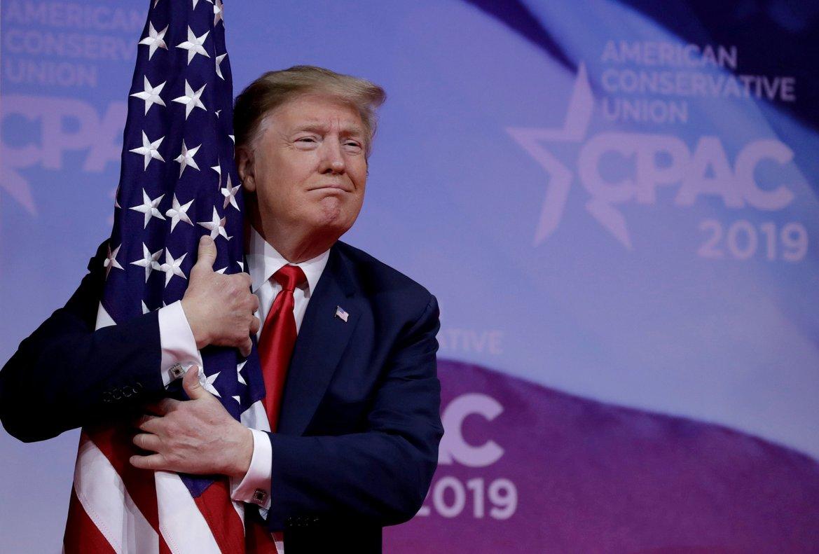 El presidente Donald Trump abrazando una bandera de su país.
