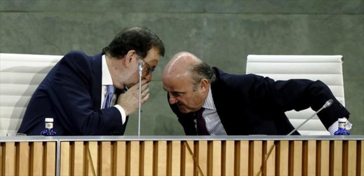 Mariano Rajoy y Luis de Guindos, en la presentación del libro España amenazada, escrito por el ministro de Economía.
