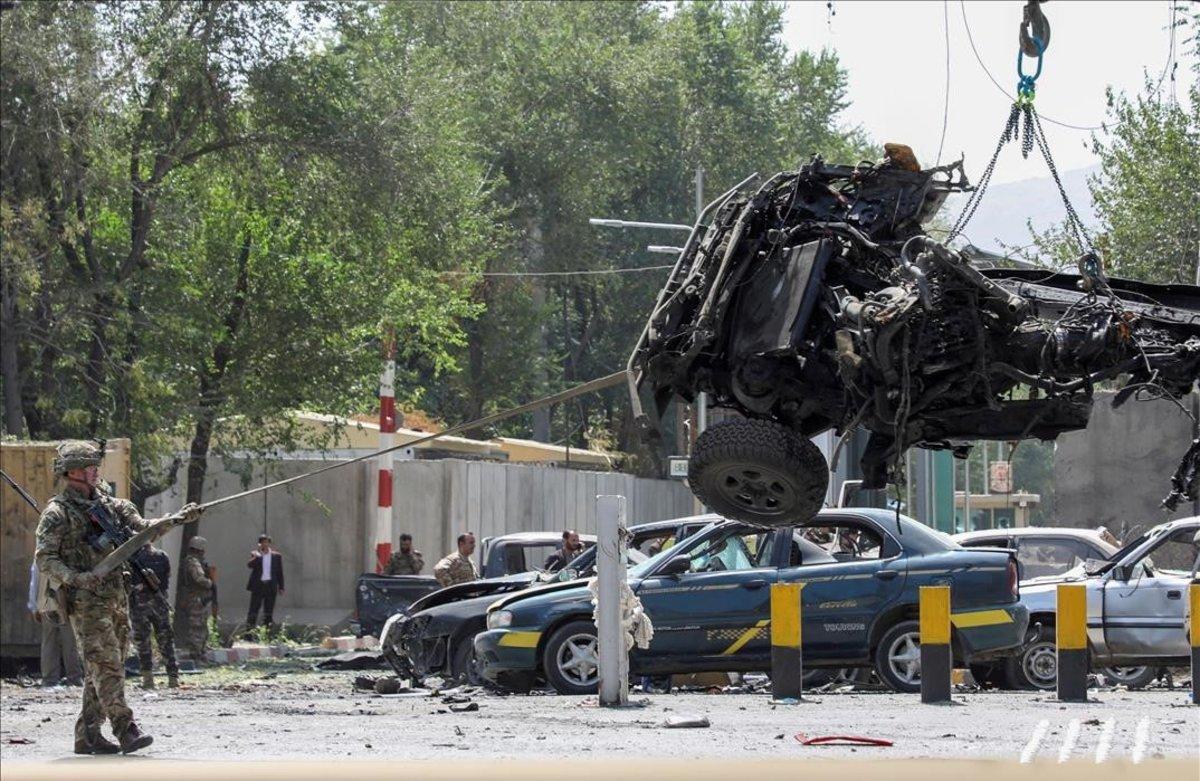 Soldados de la OTAN retiran uno de los vehículos siniestrados en un atentado suicida en Kabul.