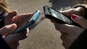 Una foto de archivo con dos personas escribiendo en sus teléfonos móviles
