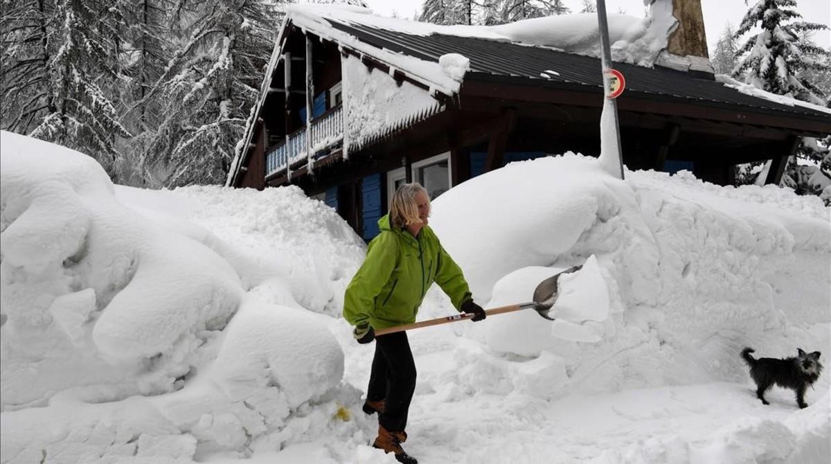 Una mujer limpia la nieve de los accesos a su casa en Val d'Isere, en los Alpes franceses.