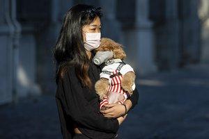 Una mujer y su mascota, con mascarillas, en la ciudad china de Guangzhou.