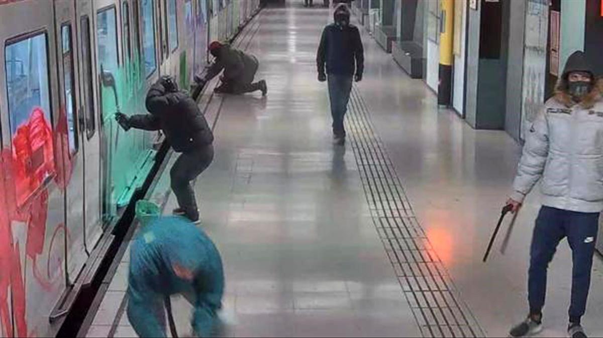 Unos grafiteros pintan un vagón del metro en una estación de Barcelona.