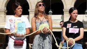 Tres jóvenes de UGT atadas de manos en una venta de esclavos simbólica en Plaza Reial para denunciar el trabajo precario de los becarios.
