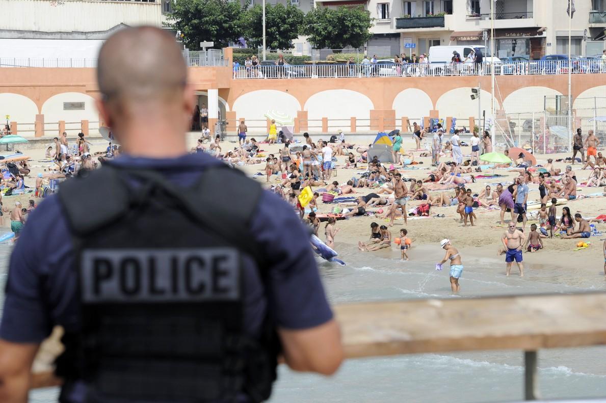 Un policía fuertemente armado patrulla por una playa de Marsella.