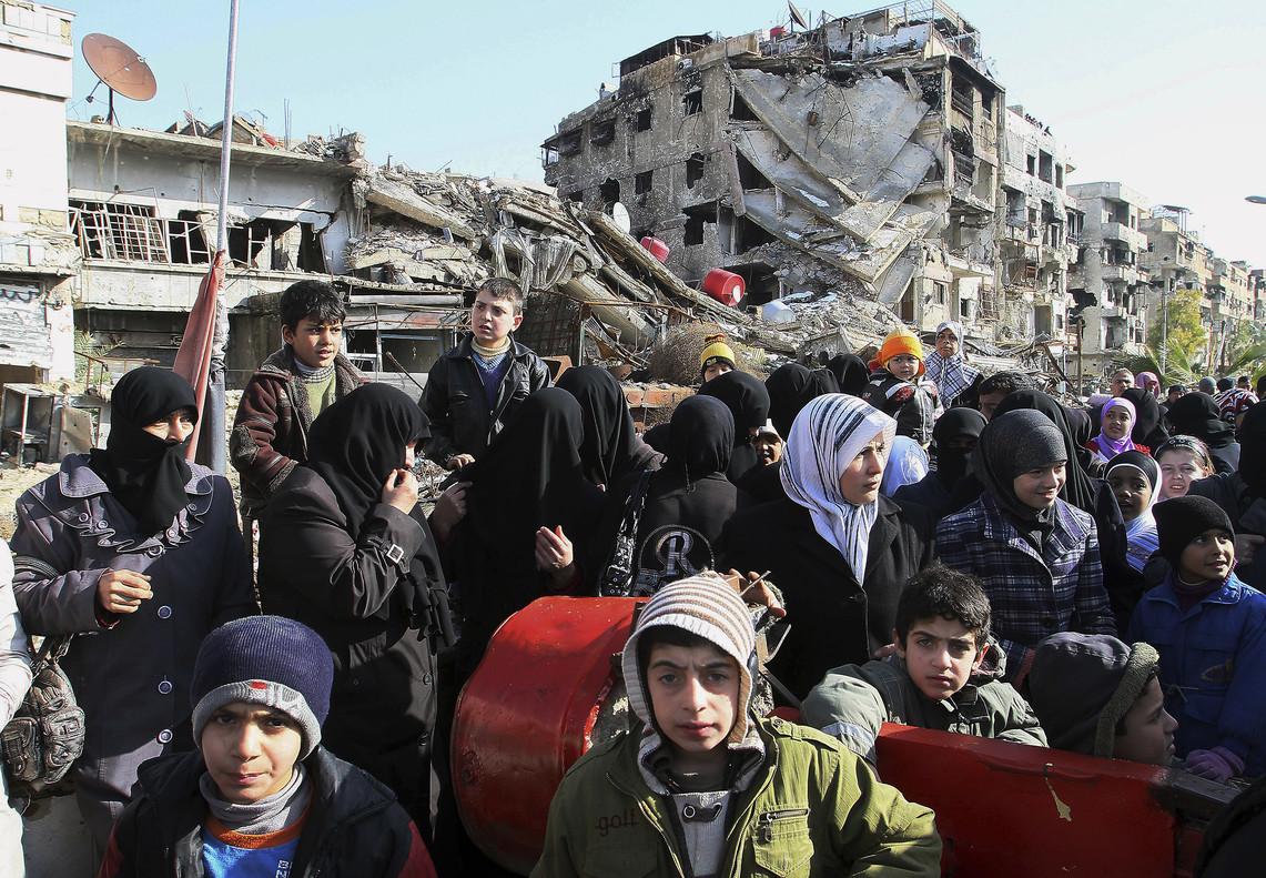 Decenas de sirios hacen cola para recibir comida en las afueras de Damasco.