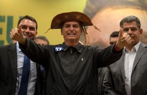 Brazil s right-wing presidential candidate for the Social Liberal Party  PSL   Jair Bolsonaro  C   gestures flanked by his son and Rio de Janeiro s elected Senator  Flavio Bolsonaro  L   and the president of the Social Liberal Party  PSL   Gustavo Bebianno  during a press conference in Rio de Janeiro  Brazil  -   Photo by Mauro Pimentel   AFP