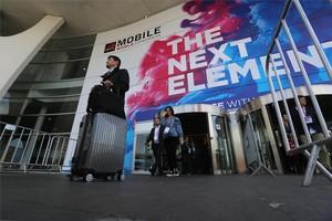 Asistentes salen con maletas del Mobile World Congress del 2017.