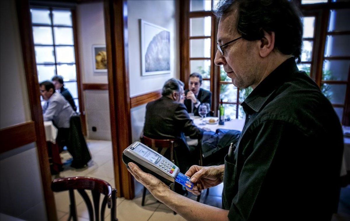 Un camarero cobra una cuenta en un restaurante de Barcelona.