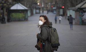 Una mujer con mascarilla en la Rambla vacía.