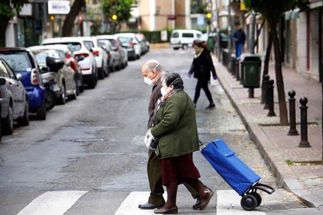Personas mayores van a la compra con mascarillas para protegerse del coronavirus, en Córdoba.