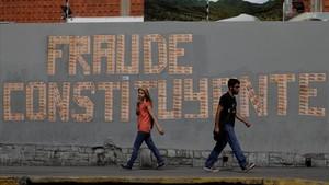 Dos personas pasan junto a un grafito contrario a las elecciones constituyentes, en Caracas, el 26 de julio.