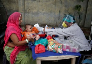 FILE PHOTO: A doctor wearing a protective face shield uses an infrared thermometer to measure the temperature of a child at his mobile health clinic, after his clinic and its adjoining areas were declared a micro-containment zone, after authorities eased lockdown restrictions that were imposed to slow the spread of the coronavirus disease (COVID-19), in Ahmedabad, India, June 15, 2020. REUTERS/Amit Dave/File Photo