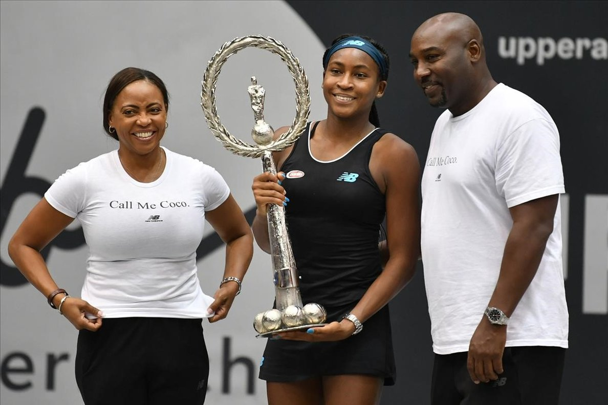 Gauff muestra feliz su primer trofeo junto a sus padres, en Linz.
